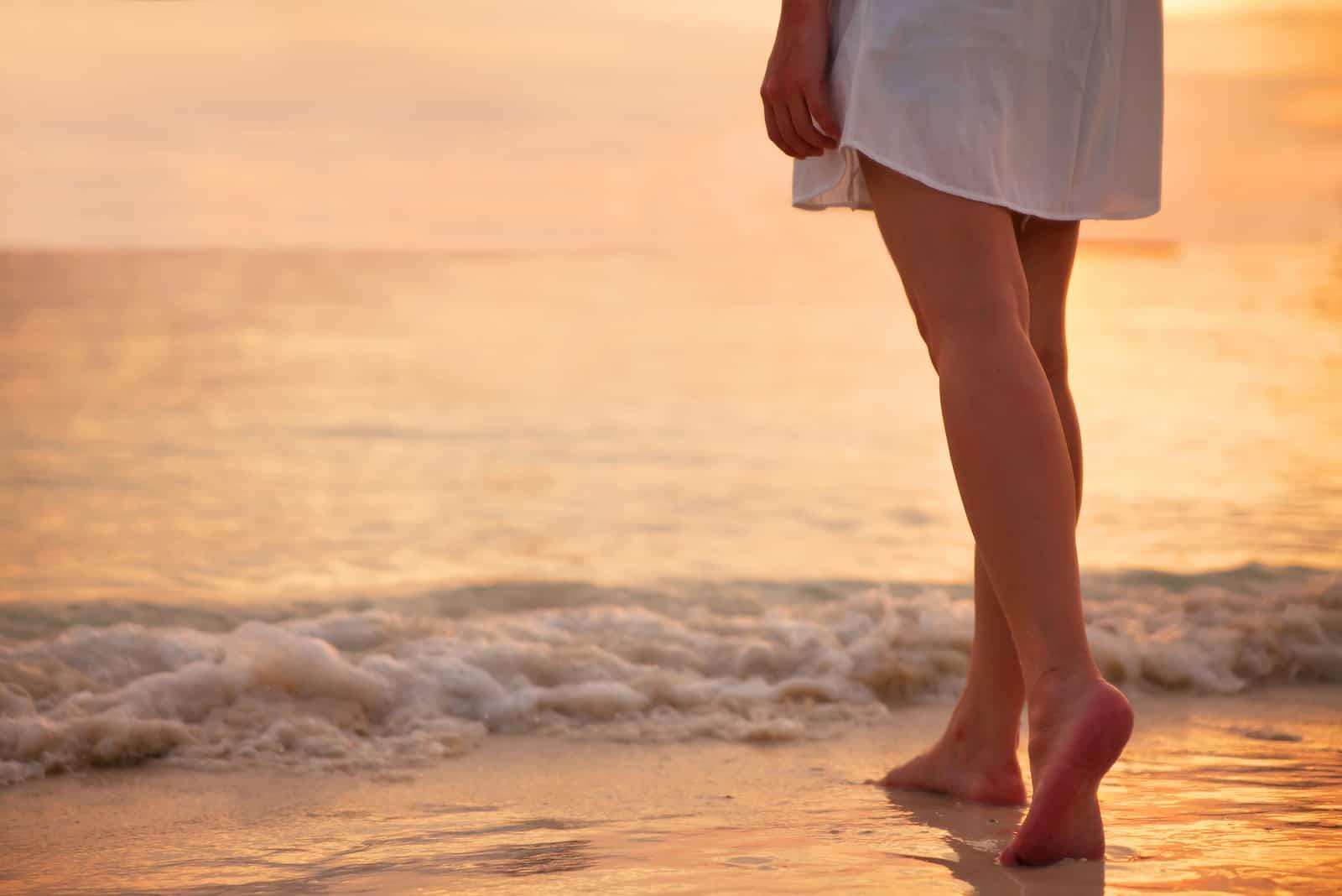 Ung kvinde i hvid kjole, der går alene på stranden i solnedgangen