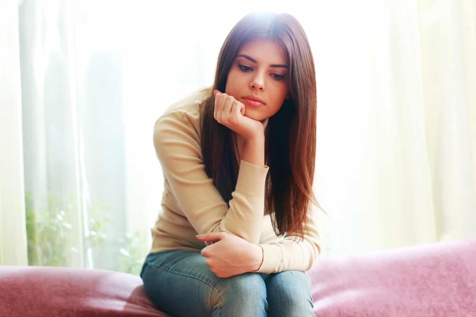 trist kvinde sidder på sengen