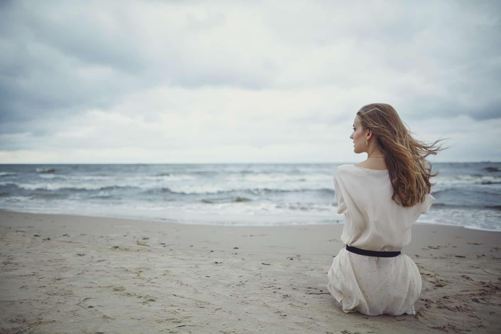 kvinde sidder på stranden alene