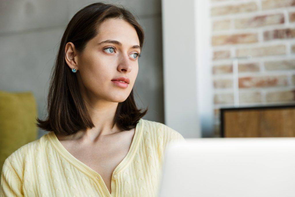 Attraktiv ung brunette kvinde bruger bærbar computer, mens du sidder i soveværelset