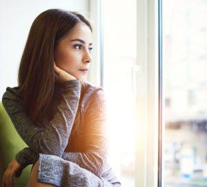 smuk kvinde kigger ud af vinduet