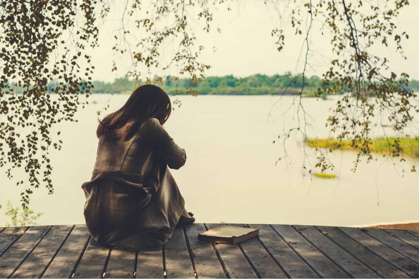 ensom kvinde, der sidder alene ved søen