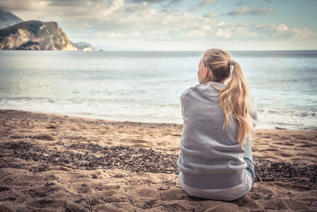 Eftertænksom ensom ung kvinde sidder på stranden og krammer knæene