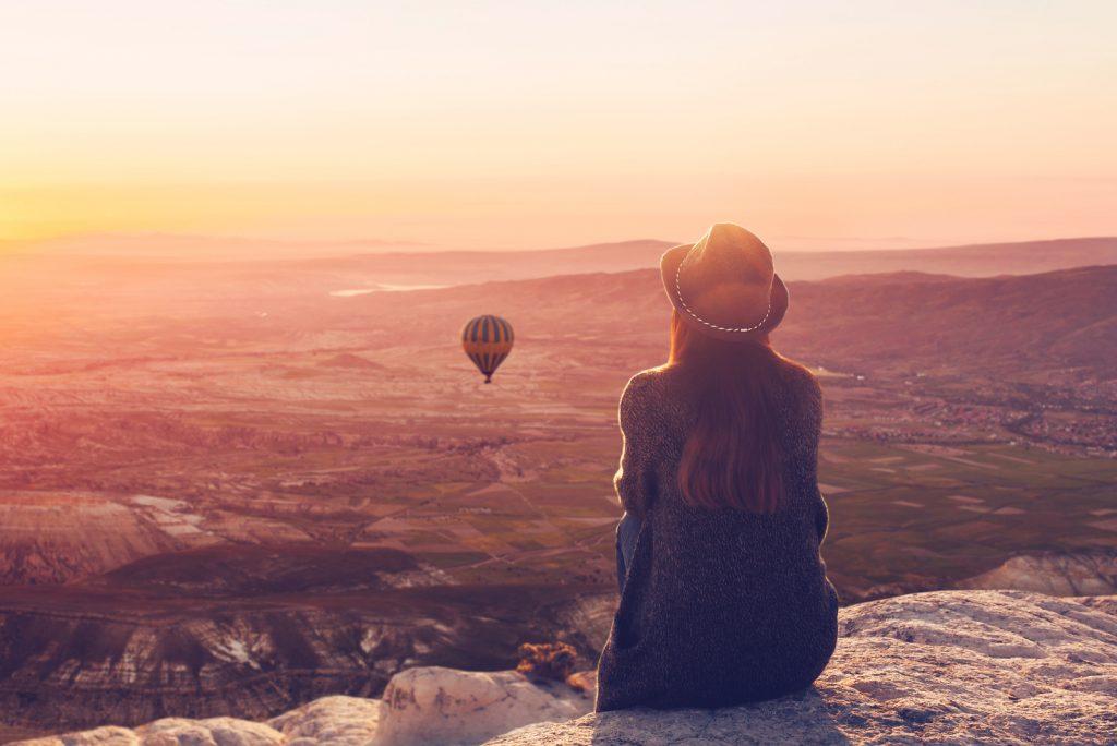 En kvinde på toppen af en bakke alene beundrer det rolige naturlige landskab