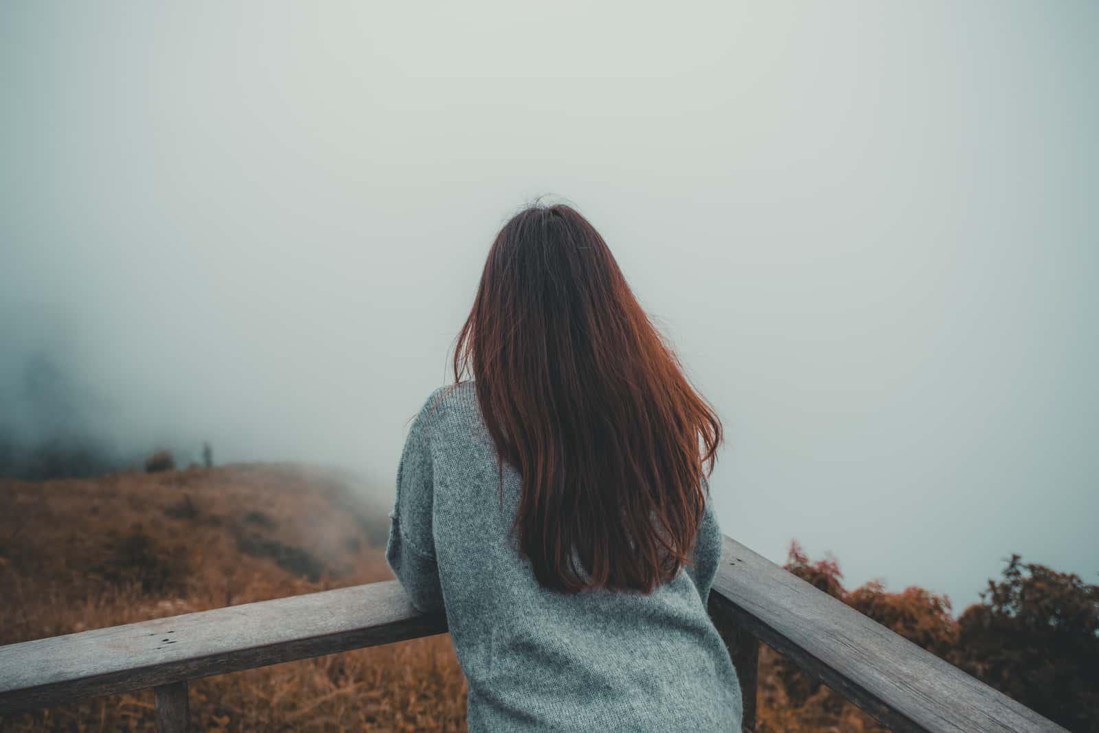 En kvinde, der står alene på balkonen og ser på hvid tåget og bjergbaggrund