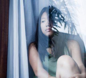 kvinde ser tankevækkende gennem vinduet