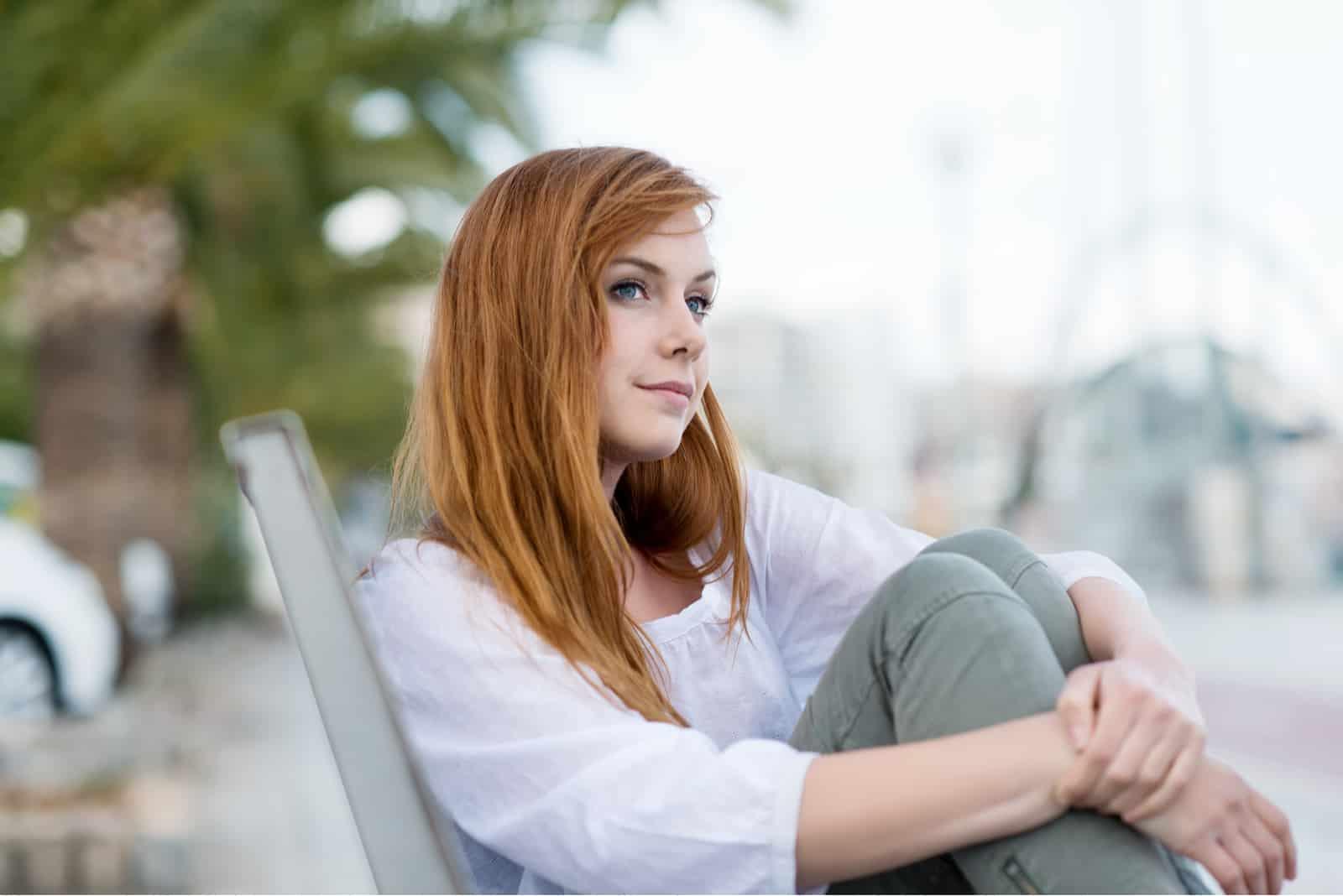 kvinde sidder på bænk i parken