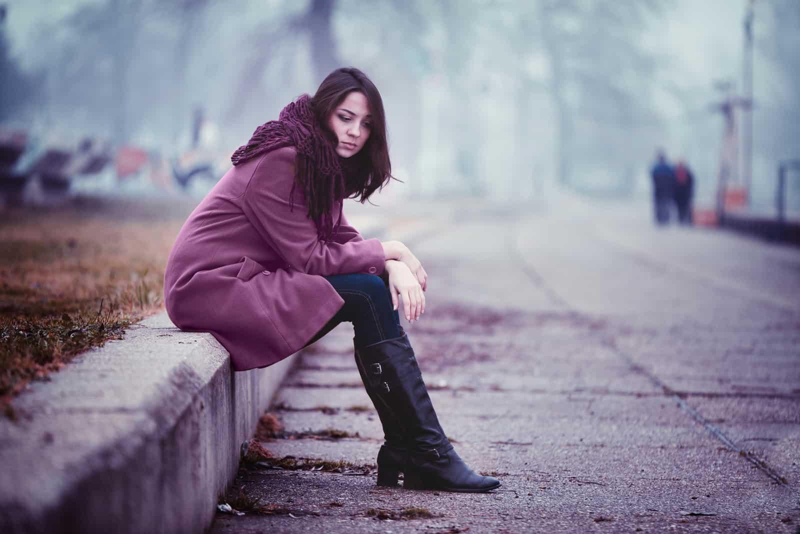 kvinde sidder alene udendørs