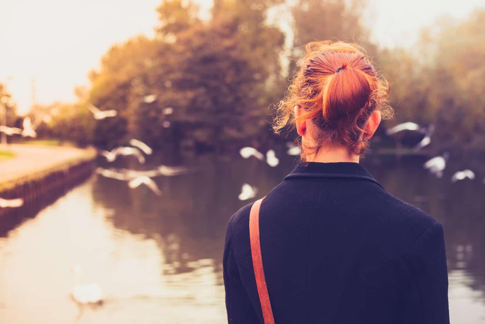 Set bagfra af ung kvinde, der ser på fugle ved en flod