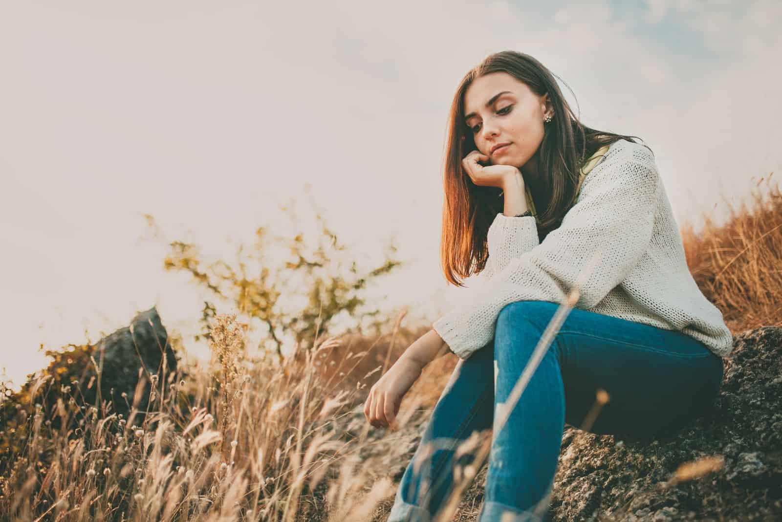 Trist ung pige, der sidder alene på en sten udendørs