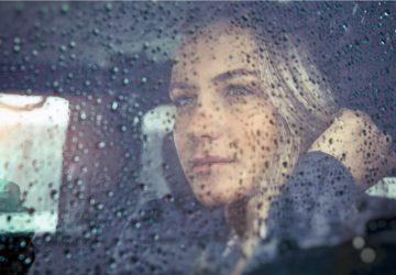 smuk trist kvinde sidder i bilen