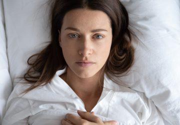 seriøs kvinde liggende på sengen