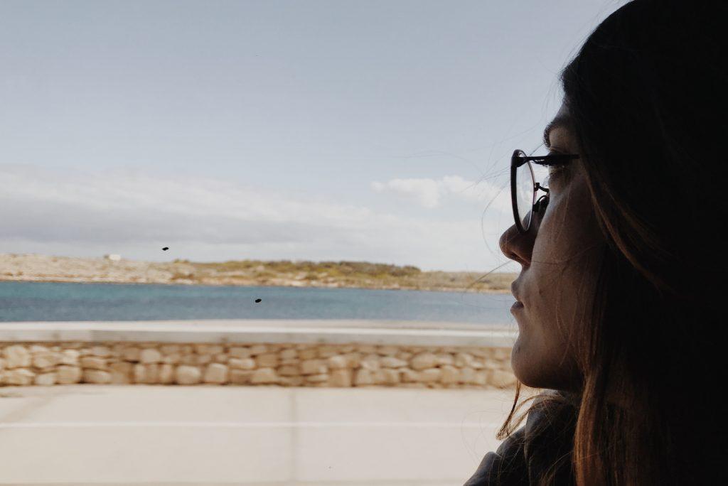 Melankolsk kvinde med briller, der rejser med tog