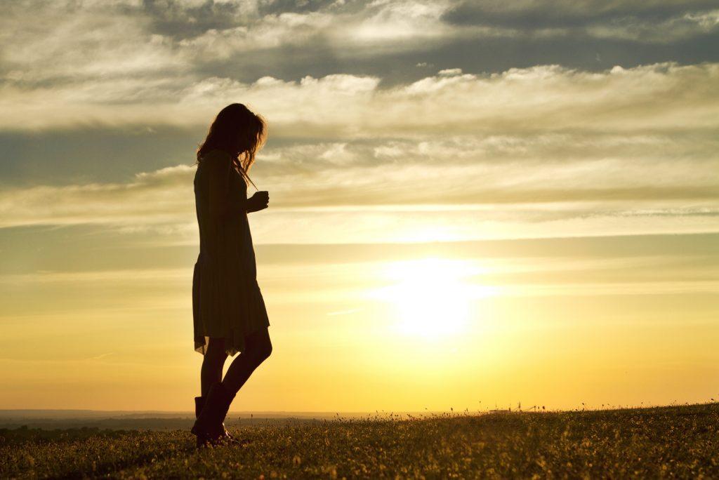 Portræt af en kvinde, der går omhyggeligt ved solnedgang
