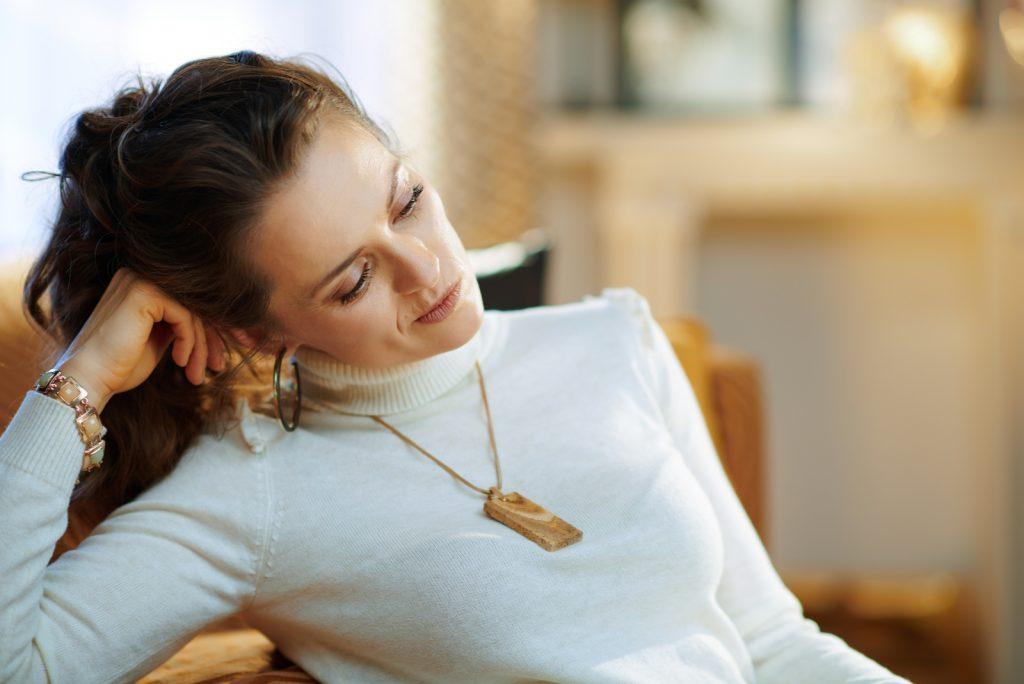 Portræt af ulykkelig moderne 40 år gammel kvinde i hvid sweater