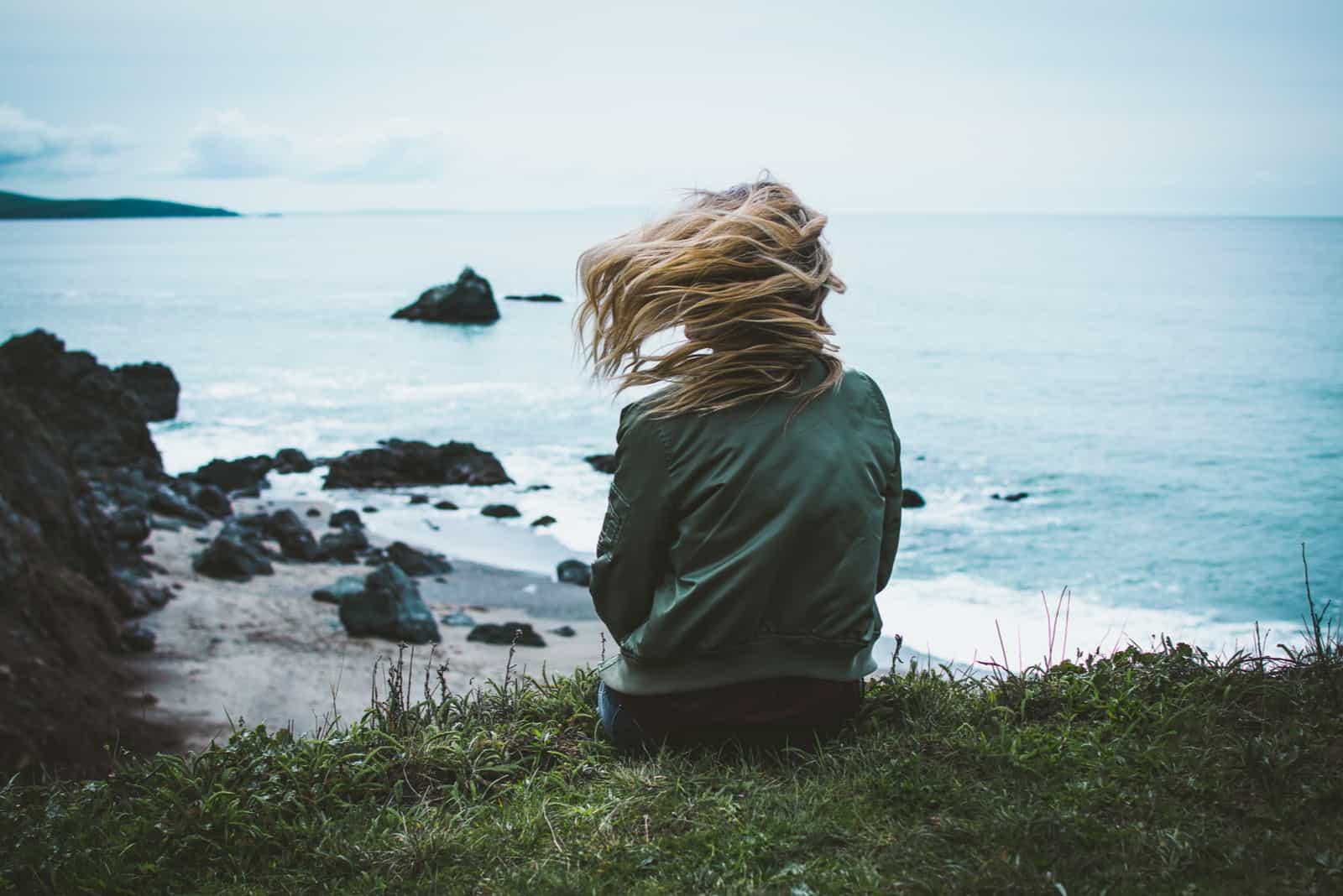 pige sidder på en klippe med udsigt over havet med håret blæser