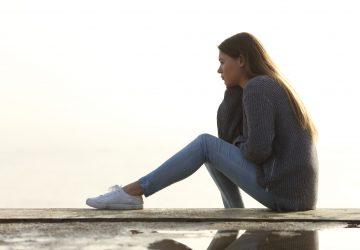 trist pige kigger væk alene sidder udendørs og overvejer horisonten