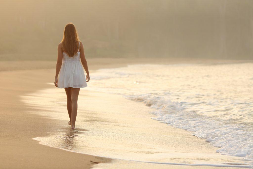 Set bagfra af en kvinde, der går på sandet ved stranden ved solnedgang