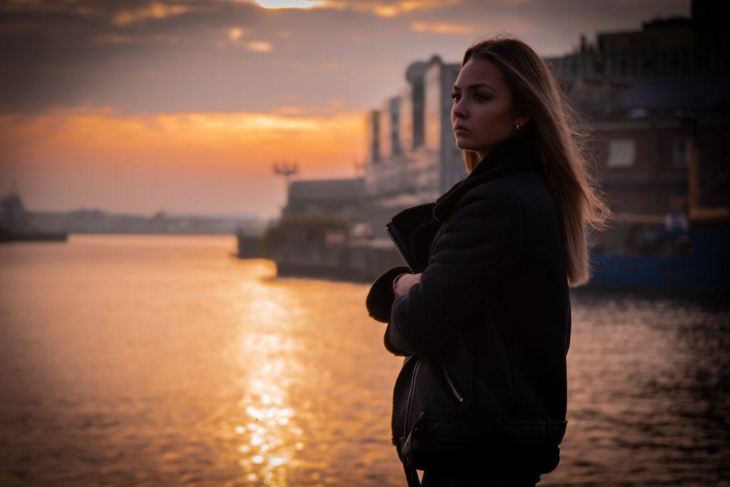 Tankevækkende pige ved solnedgangen i havnen
