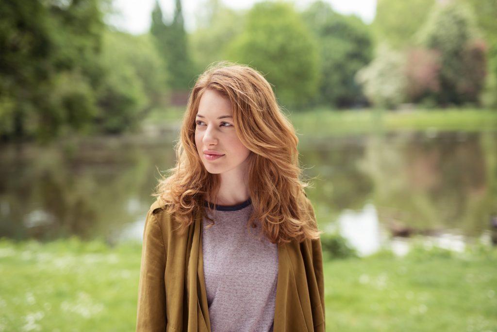 Tankevækkende temmelig blond pige, der står ved søen