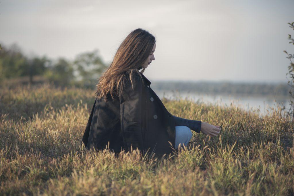 Tankevækkende trist, melankolsk pige, der sidder i græsset