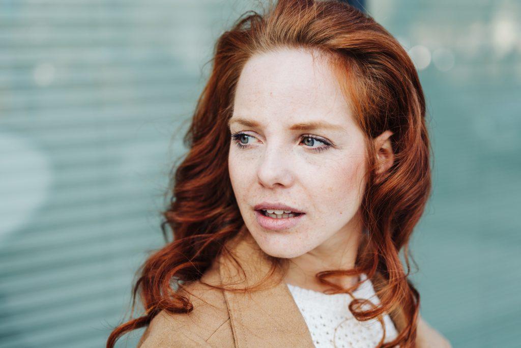 Tankevækkende ung kvinde kigger til siden med skille læber