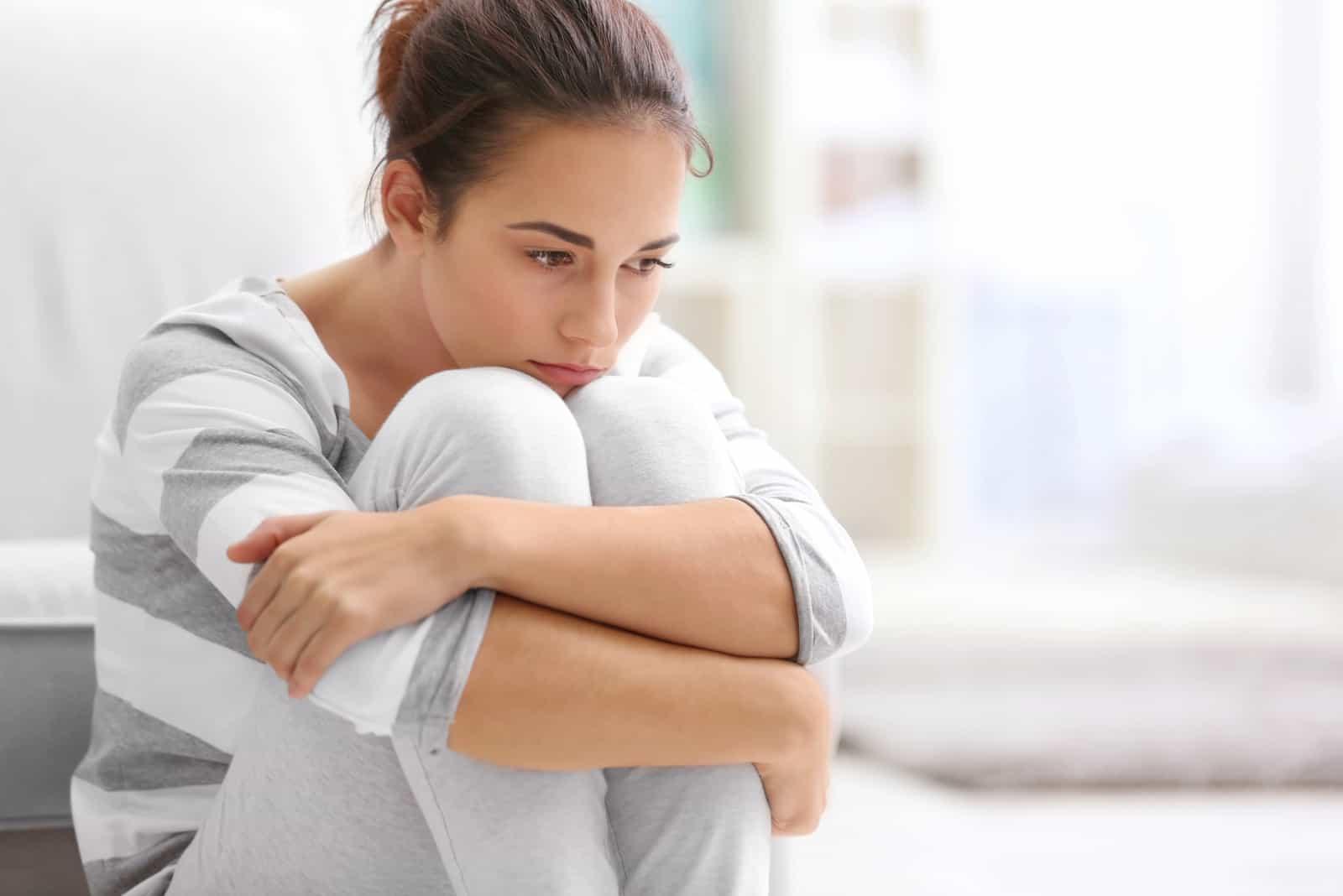 trist kvinde sidder i sofaen