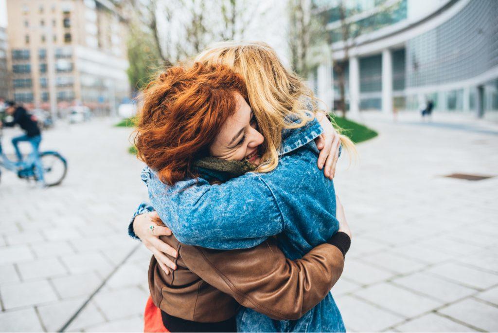 To venner rødhåret og blond pige, der mødes på gaden i byen og krammer