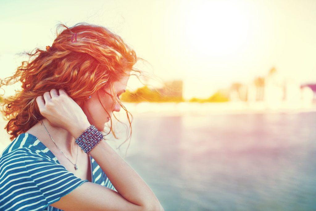 Trist rødhåret kvinde kigger væk over floden udendørs vintage