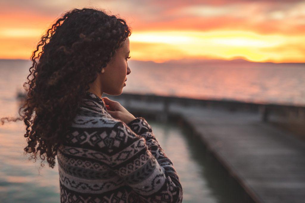 Ung afroamerikansk kvinde står på promenaden ved søen