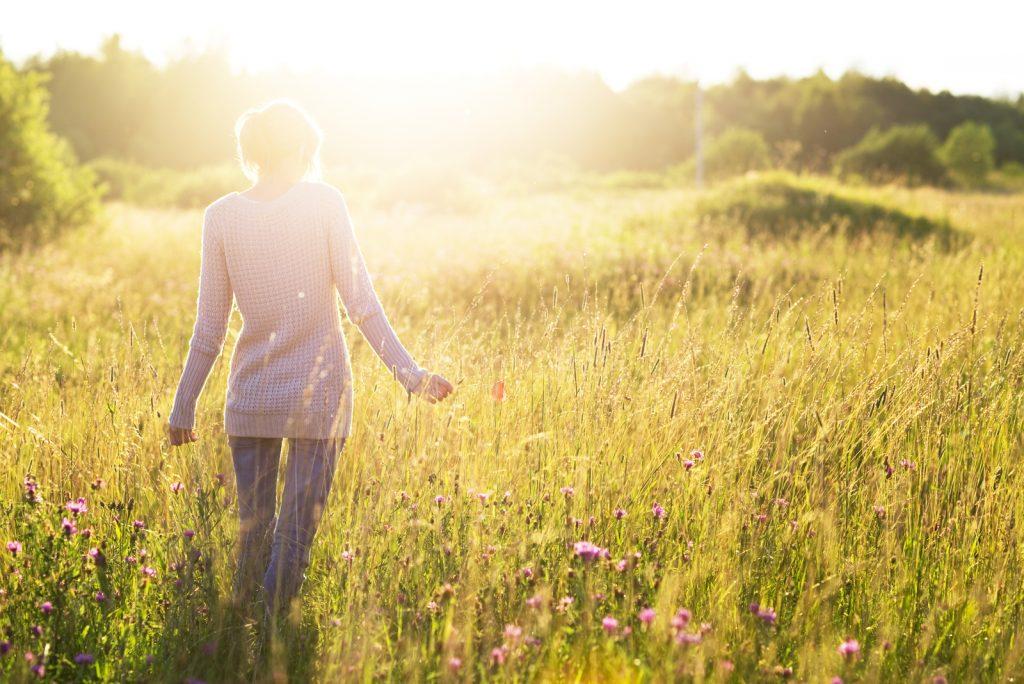 Ung kvinde, der går i marken mod solen, der holder en valmueblomst