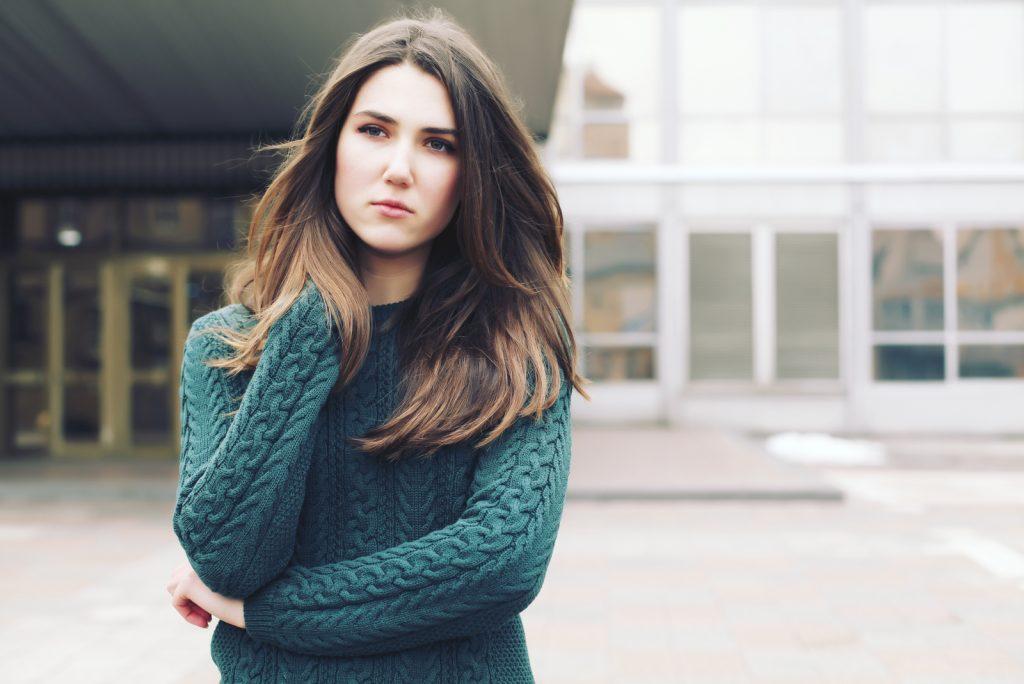 Ung kvinde iført uldgrøn sweater, der går i vintergaden