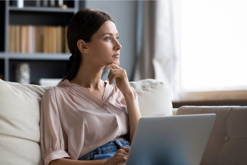 bekymret ung kvinde sidder i sofaen med en bærbar computer