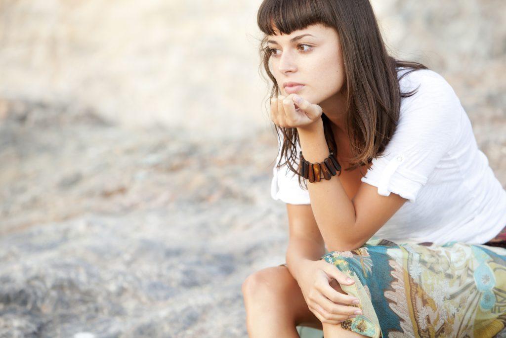 eftertænksom kvinde, der sidder alene