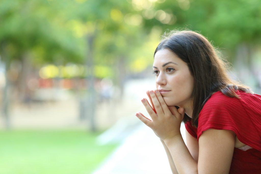eftertænksom kvinde sidder på en bænk i en park