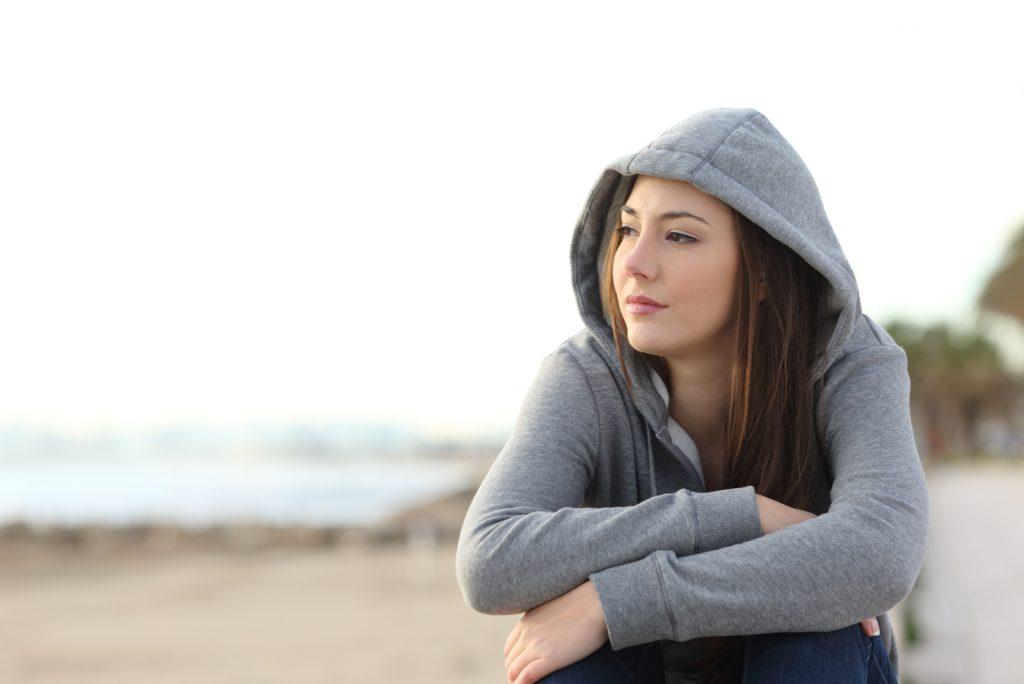 eftertænksom kvinde sidder på stranden og kigger væk