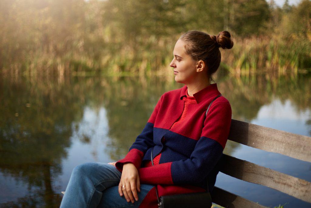 eftertænksom kvinde sidder på træbænk på bredden af __floden