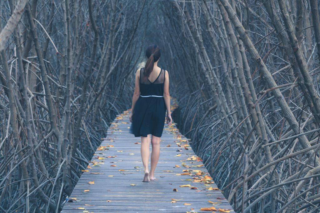ensom kvinde, der går alene på træbro ind i skoven