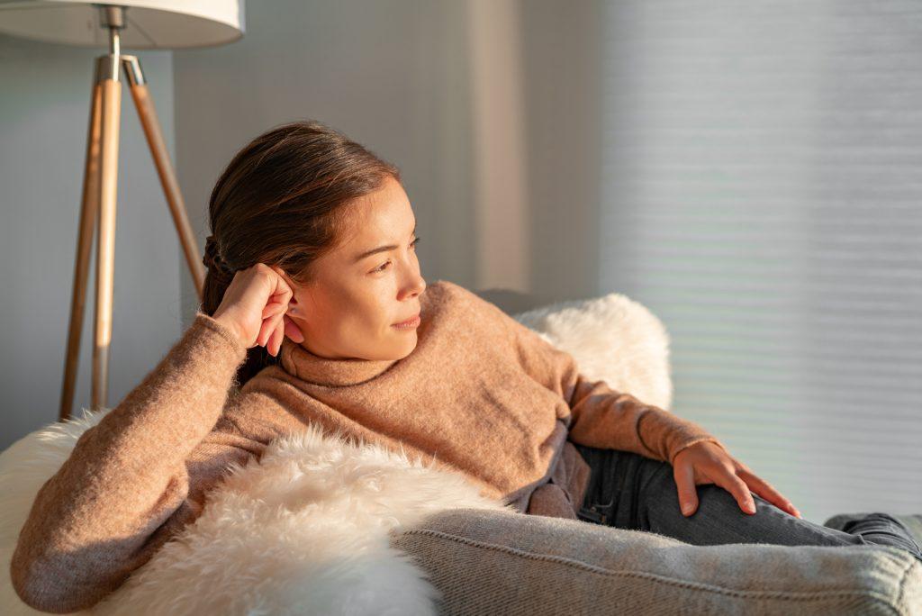 kvinde afslappende eftertænksom kigger ud af vinduet