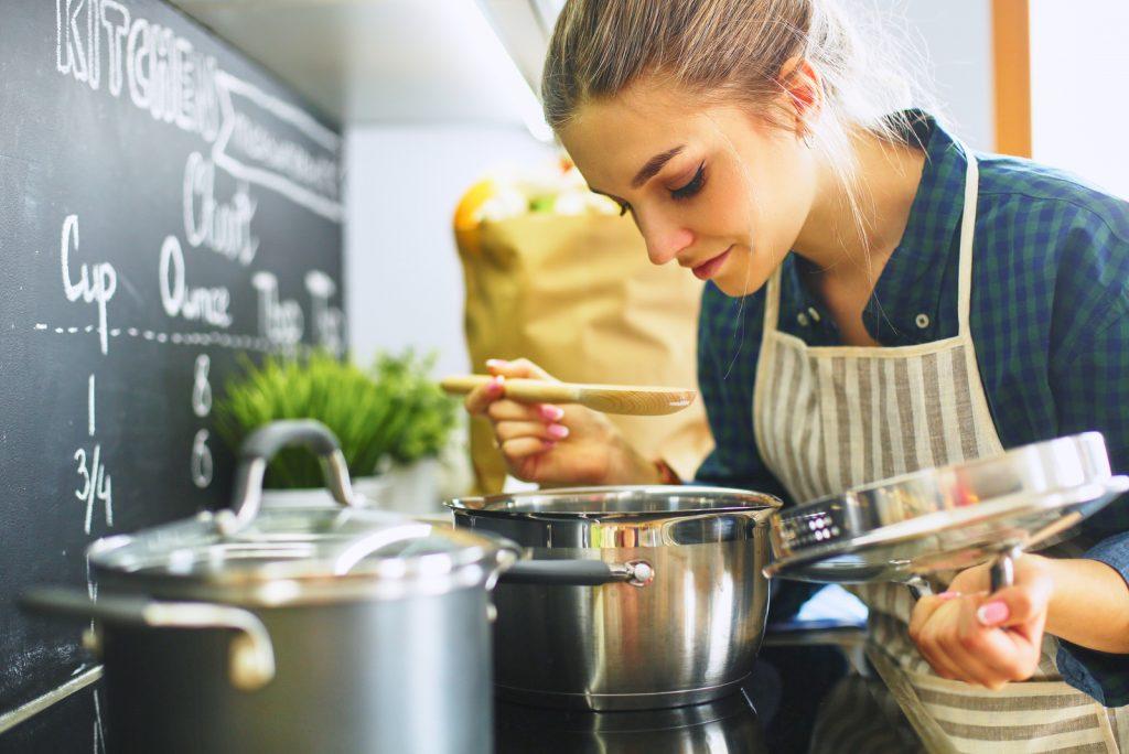 kvinde, der laver mad i sit køkken