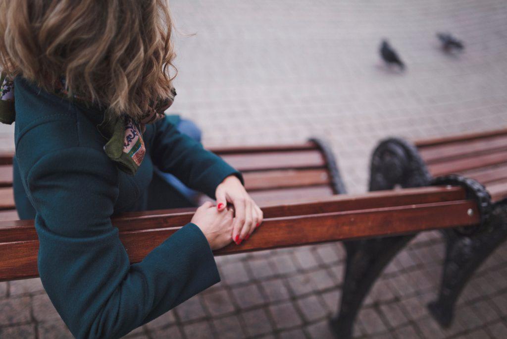 kvinde i den grønne frakke sidder tilbage på bænken