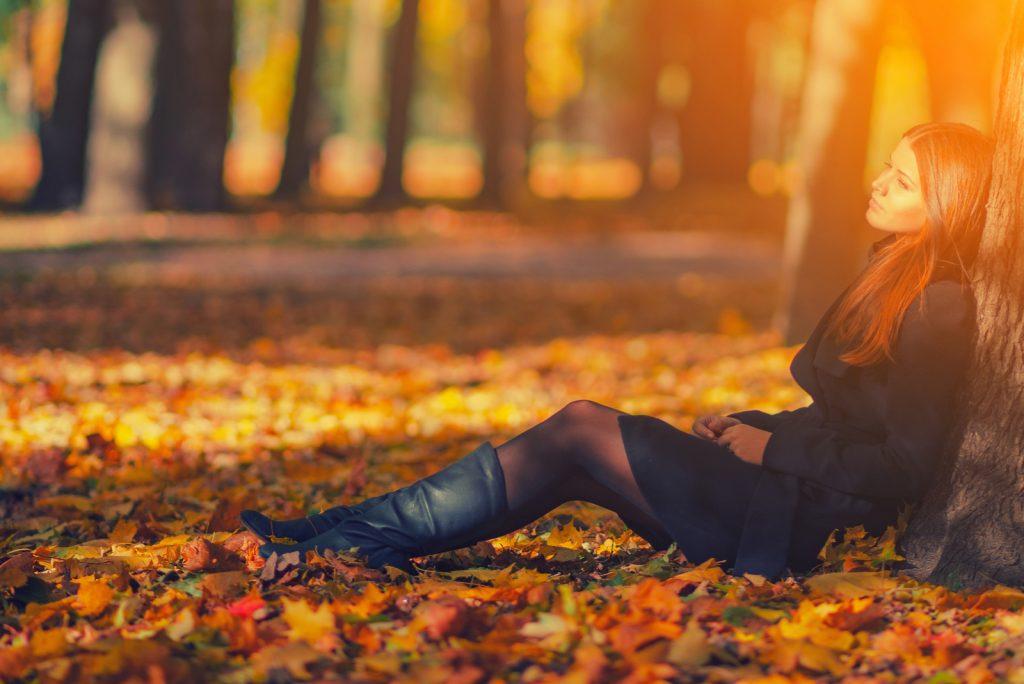 kvinde i sort frakke sidder under træet i parken