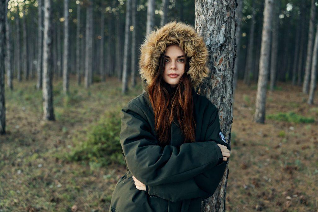 kvinde i varm jakke i skoven