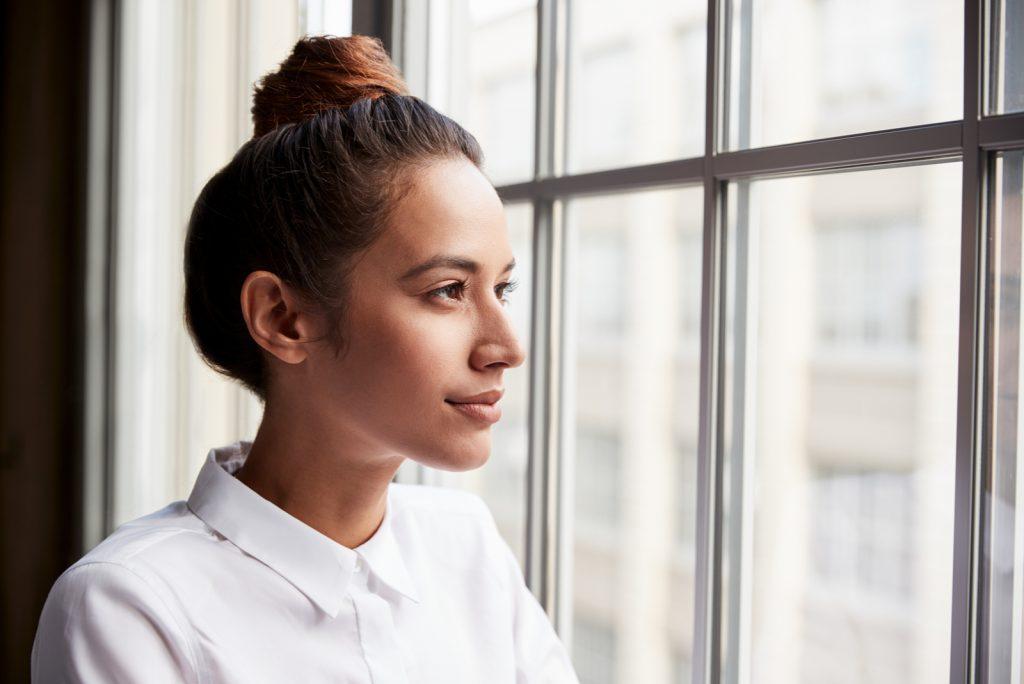 kvinde med hårbolle kigger ud af vinduet