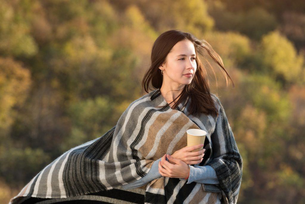kvinde pakket ind i et tæppe og ser ud i det fjerne