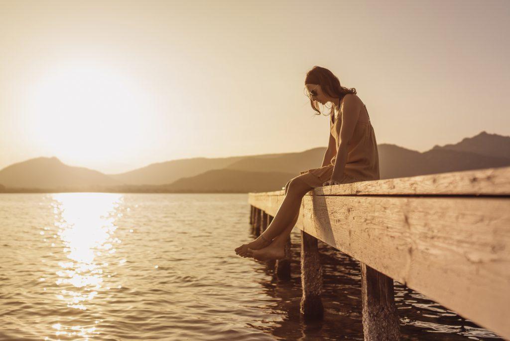 kvinde sidder på en mole ved en sø og ser ned til vandet ved solnedgang