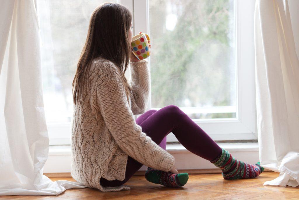 kvinde sidder ved vinduet med varm drikke