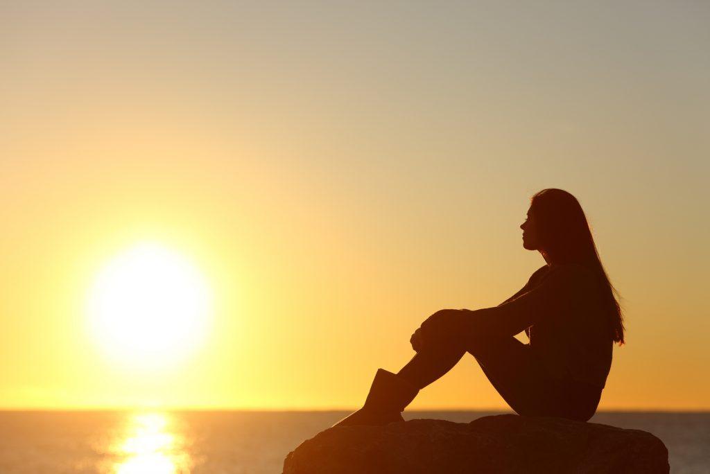 kvinde silhuet ser solen på stranden ved solnedgang