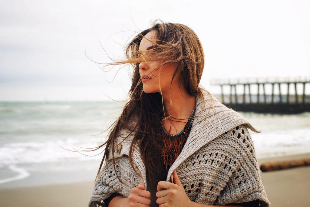 kvinde stående alene på stranden