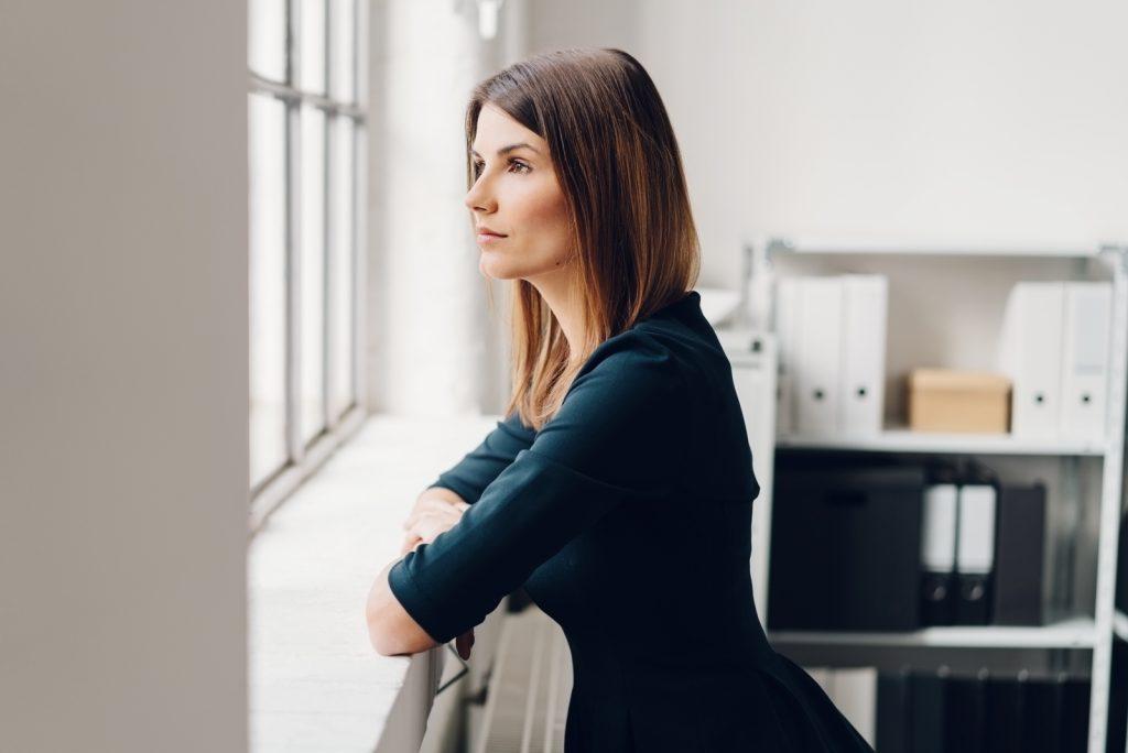 kvinde stående og stirrer ud af et vindue